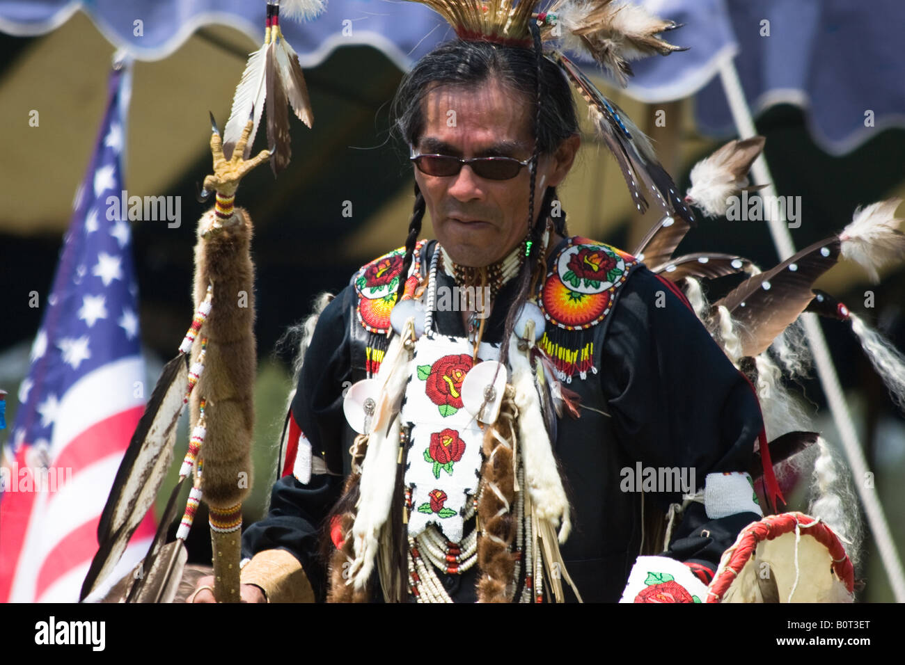 American Indian dancer, U.S. flag in the background, at the 8th Annual Red Wing Native American PowWow in Virginia - Stock Image