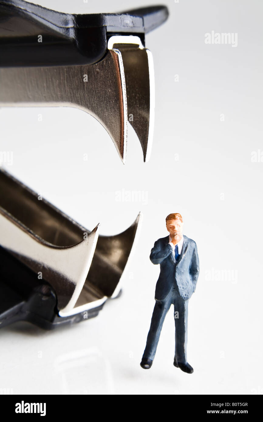 Businessman figurines standing next to a staple remover - Stock Image