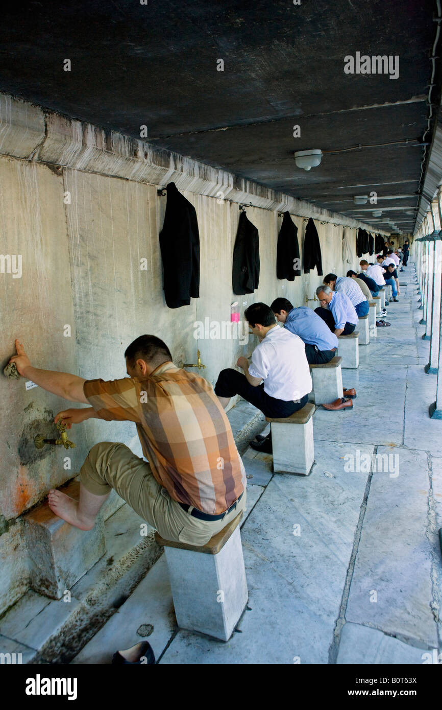 muslim men washing their feet before entering the Blue mosque for prayer in Istanbul - Stock Image
