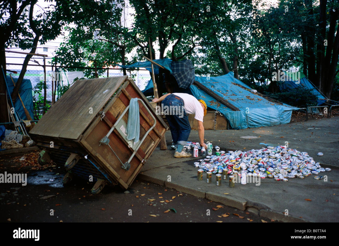 Nov 10, 2004 - Homeless man in a small park in Tokyo recycles drinking cans in order to make a little cash from - Stock Image