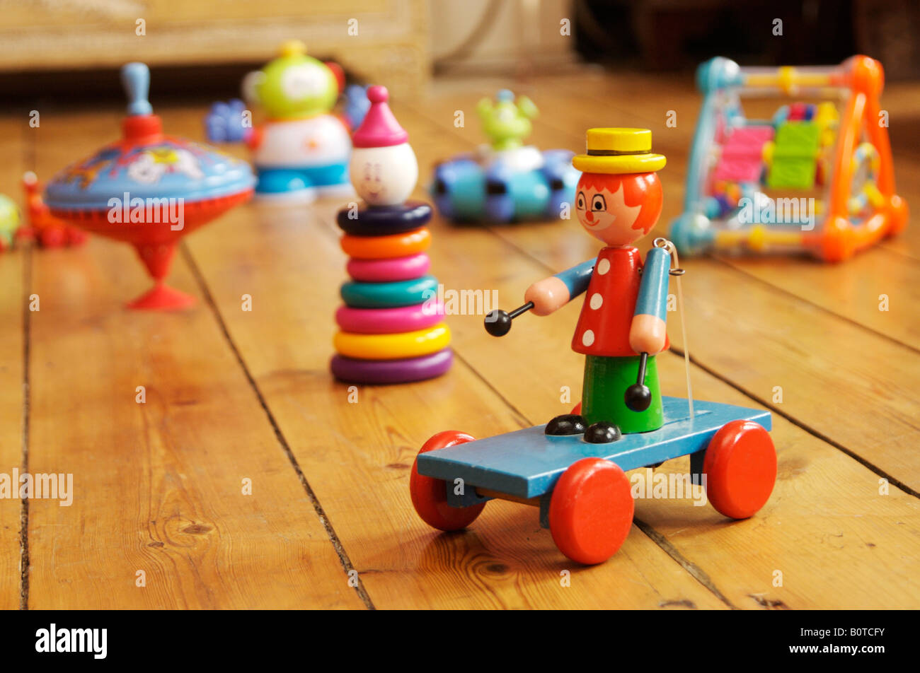 Children's toys on a wooden floor - Stock Image