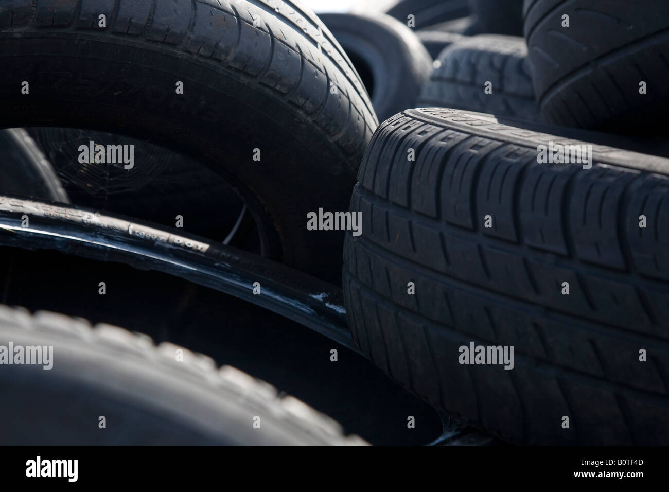 Black, part worn rubber car tyres are piled up and waiting to be recycled. - Stock Image