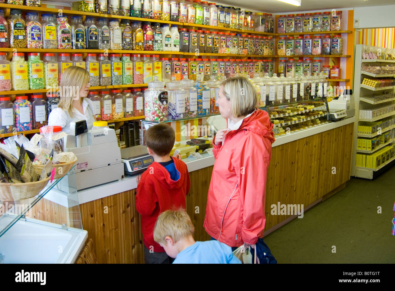 Mother And Children Buying Sweets At Traditional English Sweet Shop In The  Uk