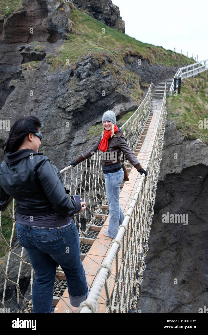 two female tourists posing on the carrick a rede rope bridge on the county antrim coast northern ireland - Stock Image