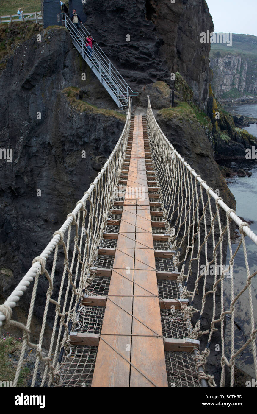 walking across the carrick a rede rope bridge on the county antrim coast northern ireland - Stock Image