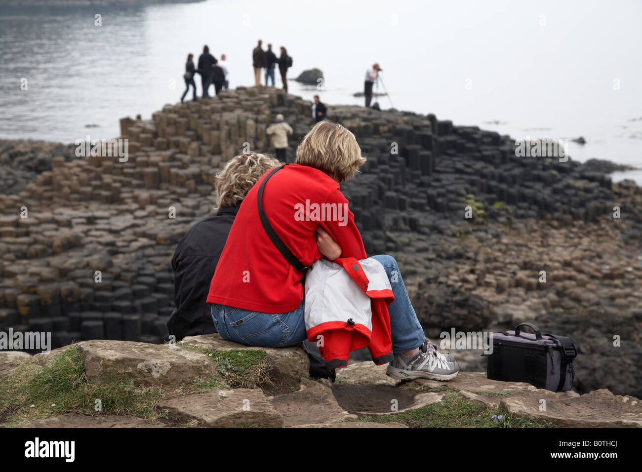 pair of blonde female caucasian tourist wearing jeans sitting watching other tourists at the giants causeway county - Stock Image