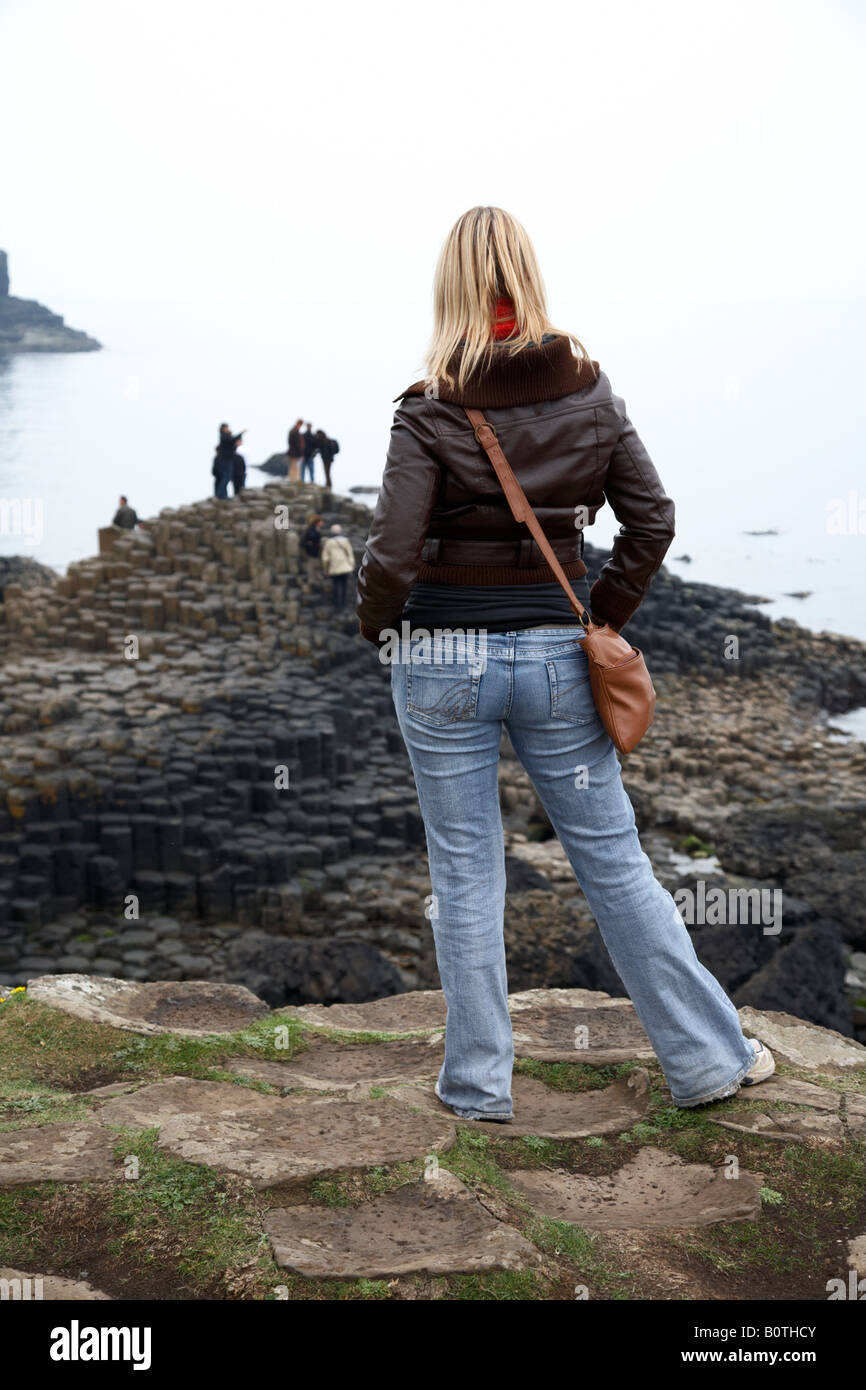 blonde female caucasian tourist wearing jeans and leather jacket standing on overcast day watching other tourists - Stock Image