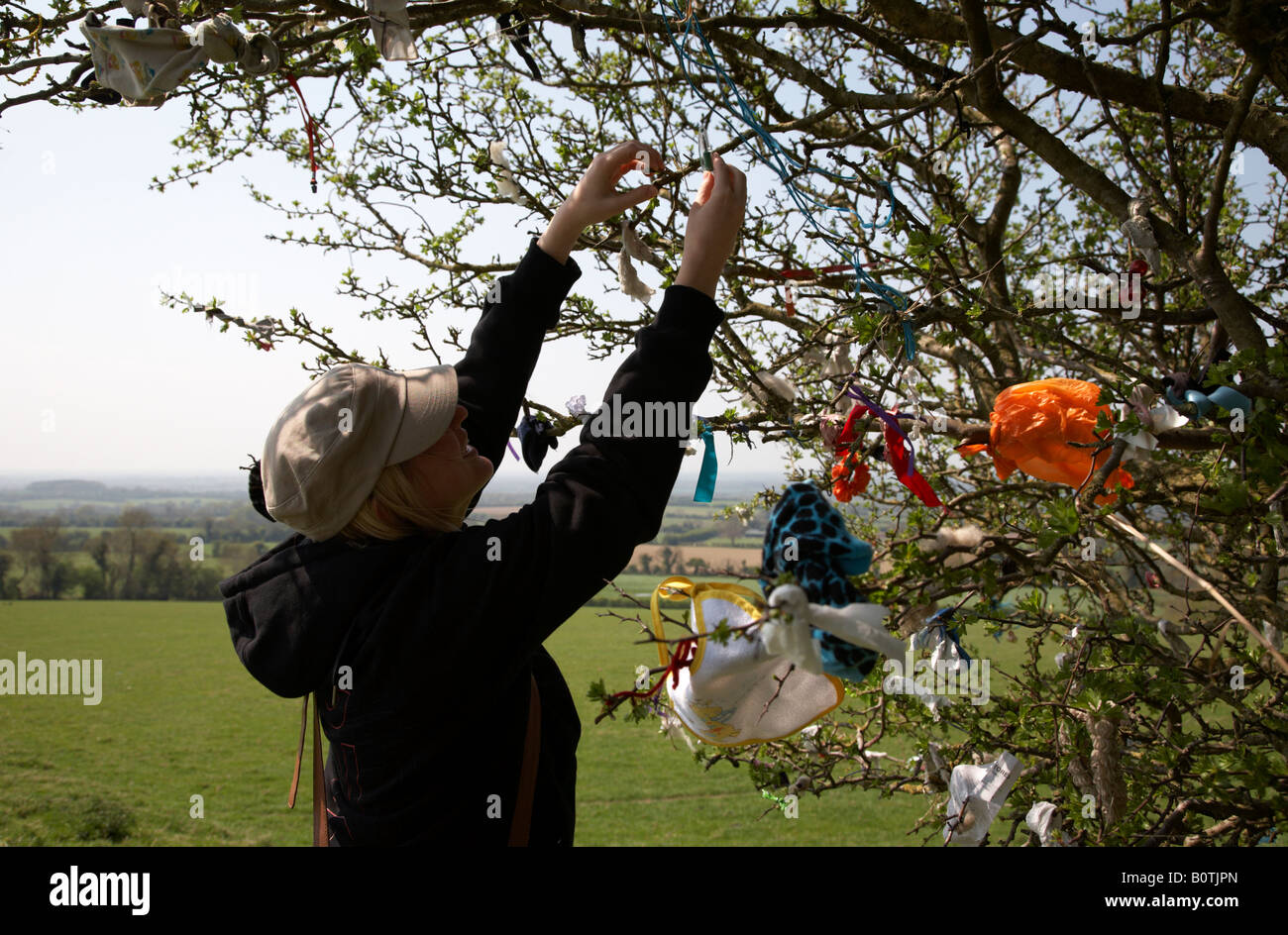 female tourist attaching offering to a fairy thorn tree on