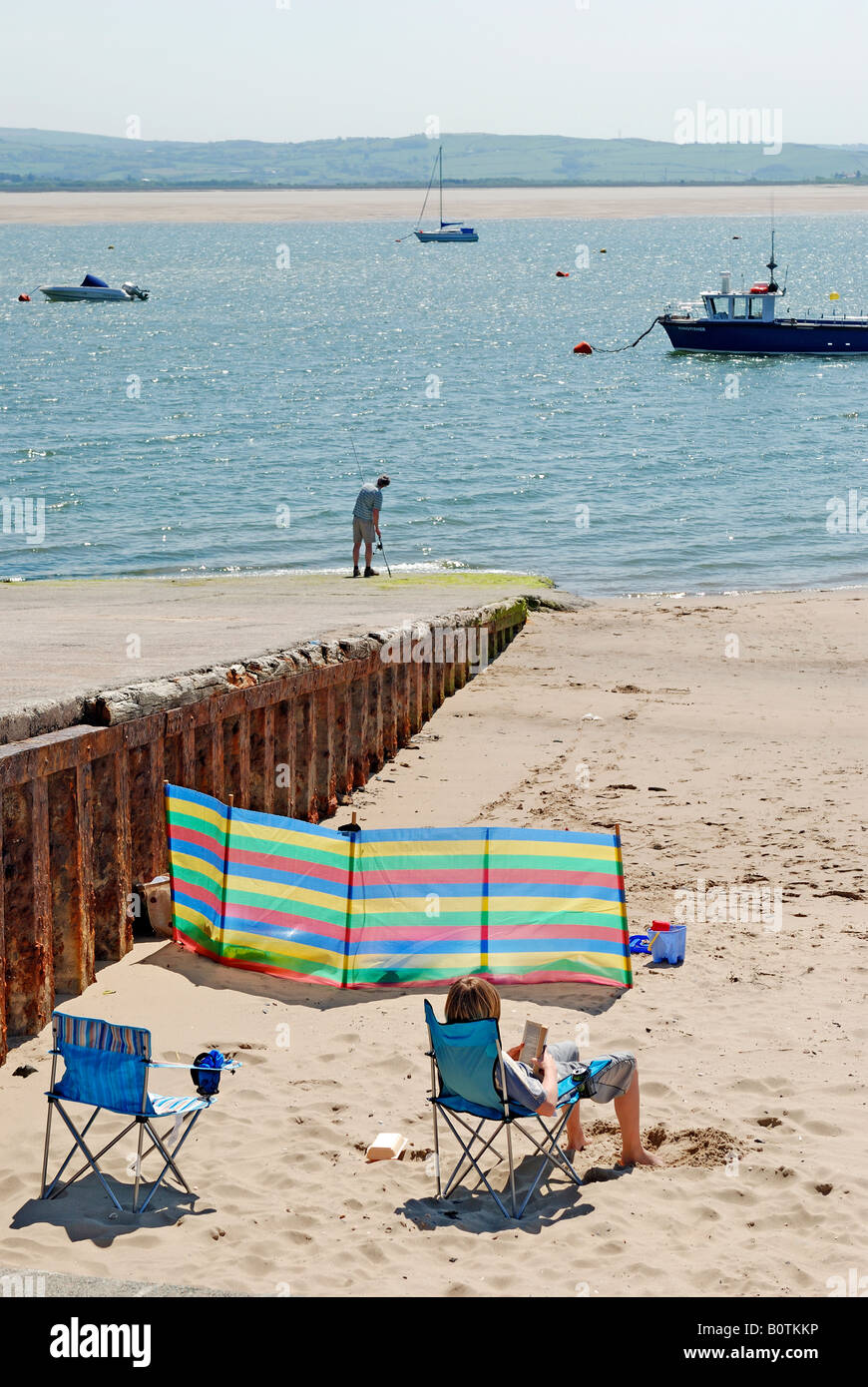 SUNBATHER WITH BOATS IN THE BACKGROUND IN THE SEASIDE TOWN OF ABERDOVEY GWYNEDD WALES Stock Photo
