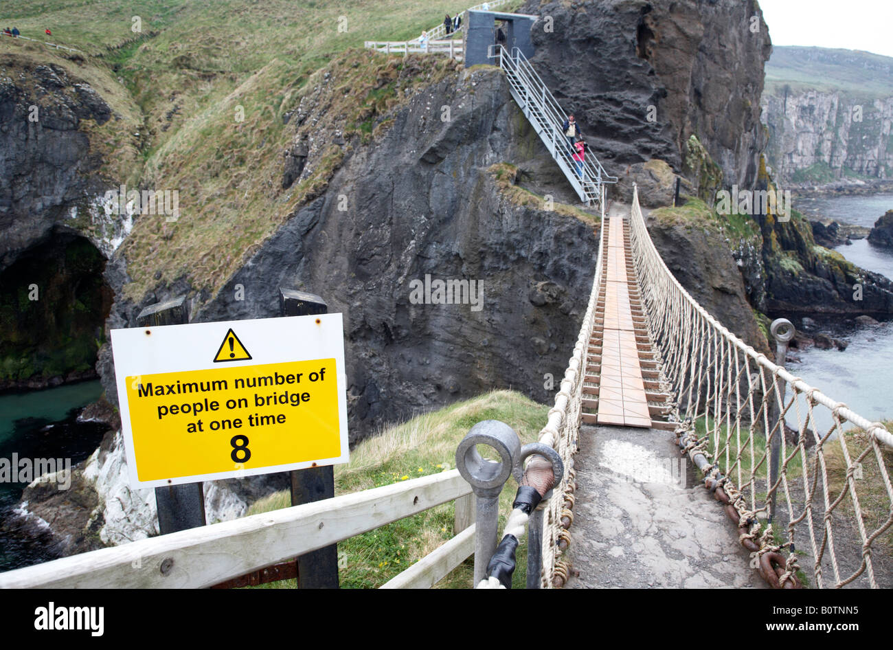 warning sign limiting the number of people who can cross the carrick a rede rope bridge at one time on the county - Stock Image