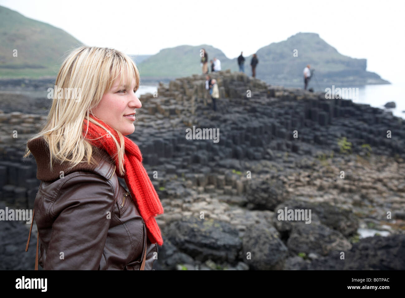 blonde north american female caucasian tourist wearing jeans red scarf and leather jacket standing on overcast day - Stock Image