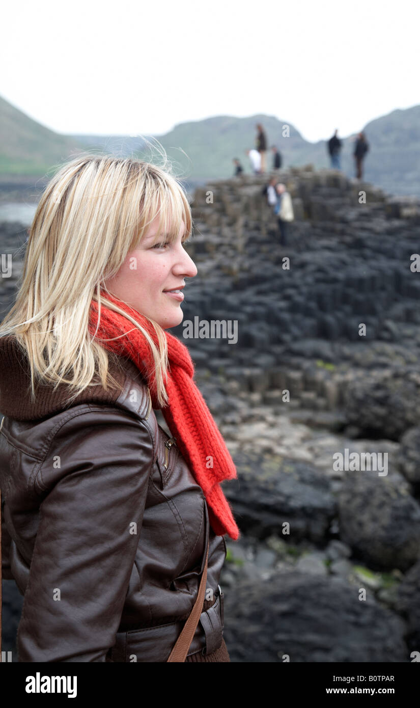 blonde female caucasian tourist wearing jeans red scarf and leather jacket standing on overcast day at the giants - Stock Image