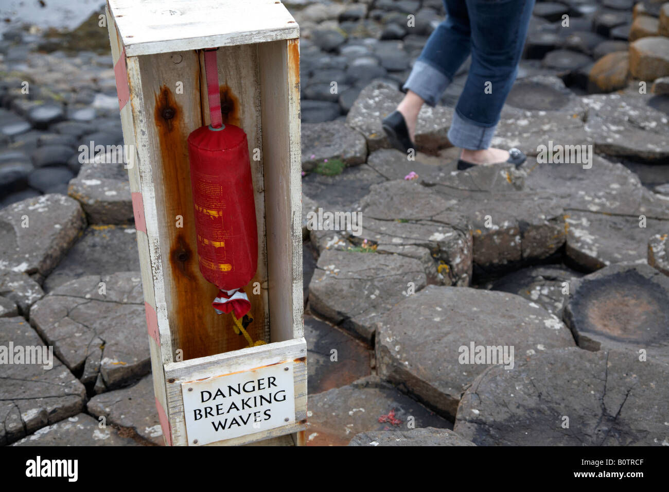 danger breaking waves sign and emergency rope with woman walking away at the giants causeway county antrim northern - Stock Image