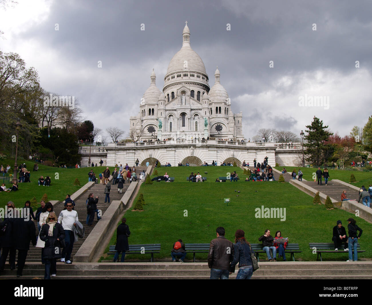 Sacre Coeur holy heart church in Montmartre Paris France with many people tourists on the steps and grass - Stock Image