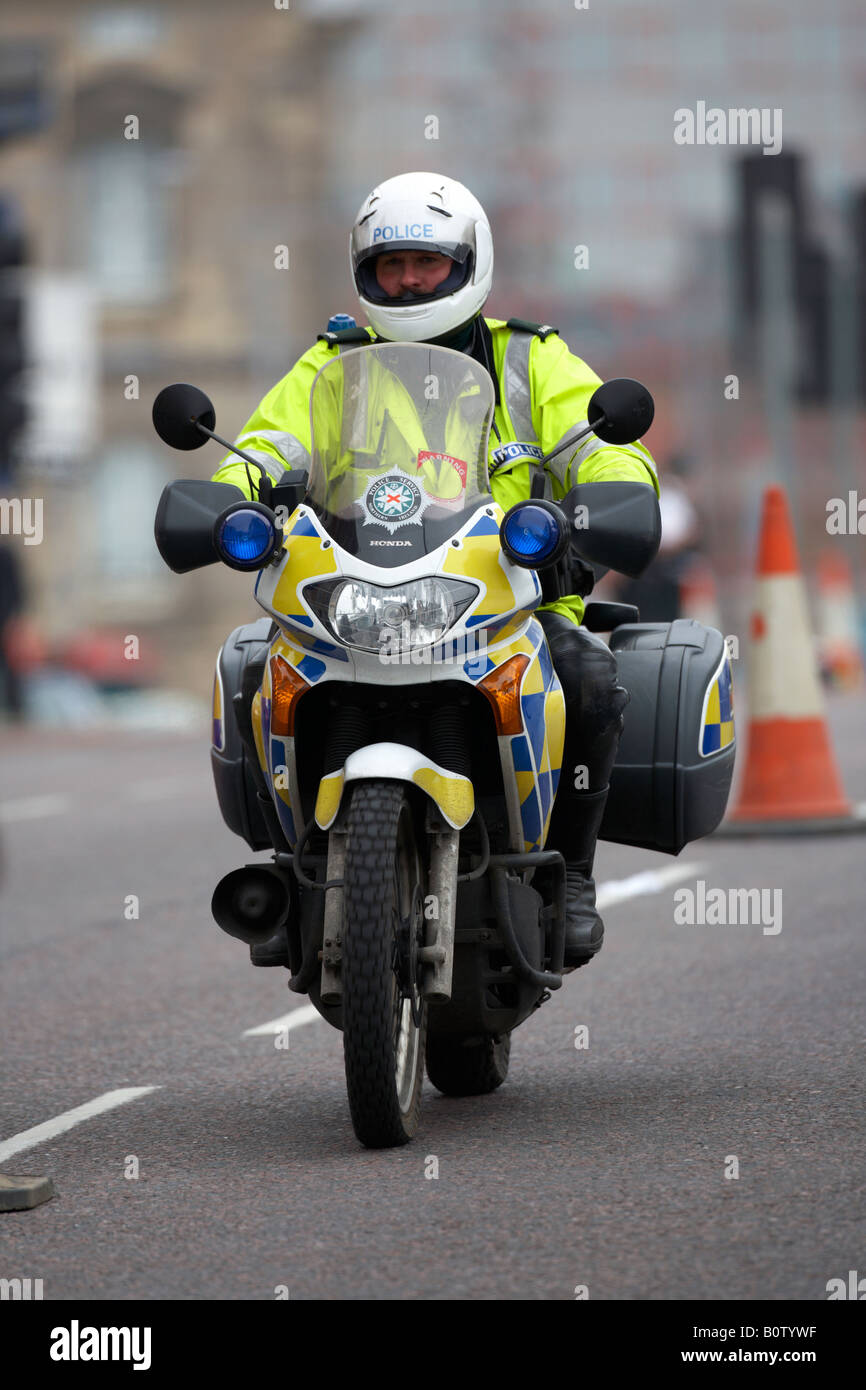 PSNI police service northern ireland motorcycle officer on patrol wearing helmet driving through city centre Stock Photo
