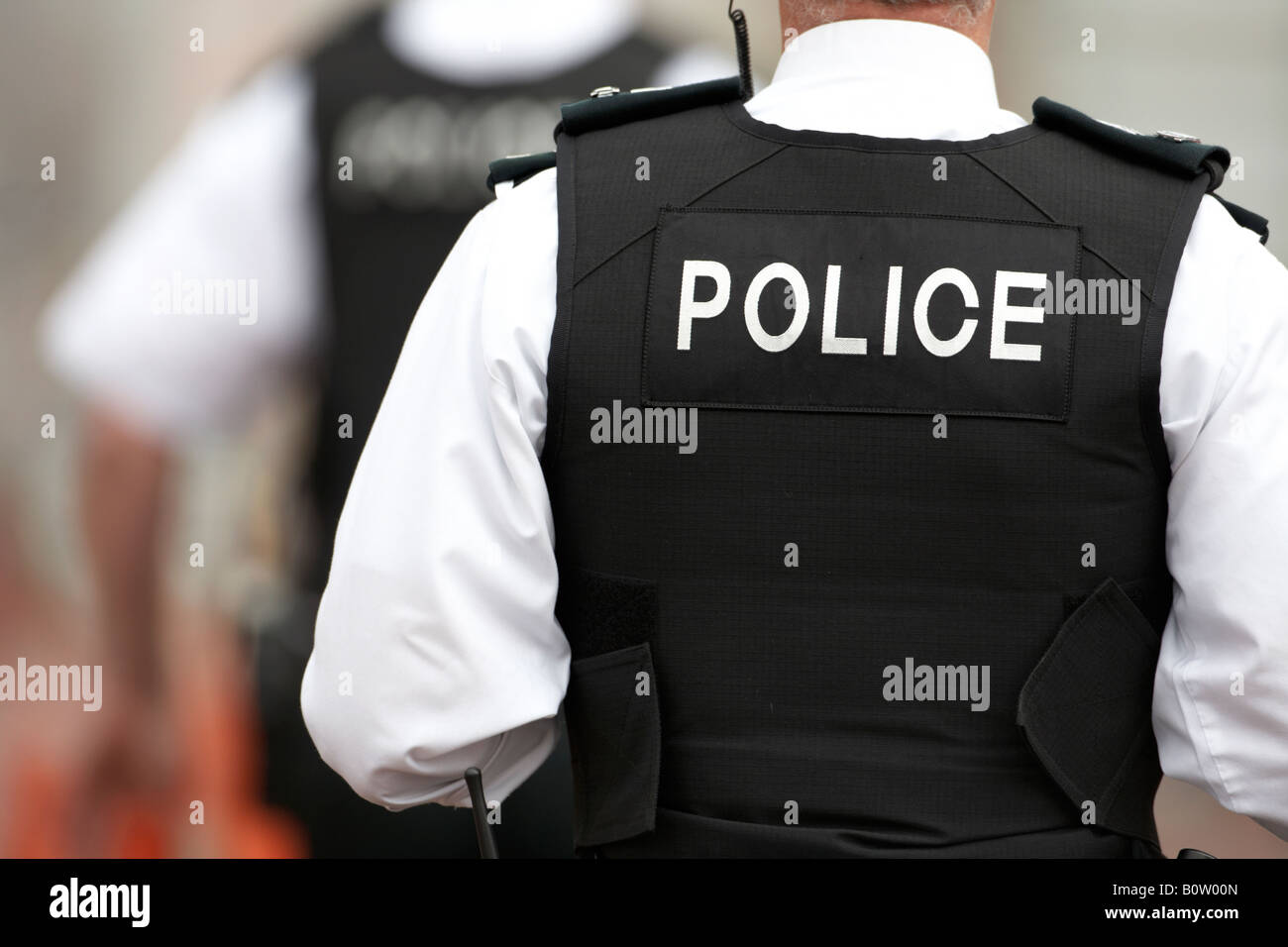 male PSNI police service northern ireland sergeant on patrol with colleague wearing stab proof vests - Stock Image