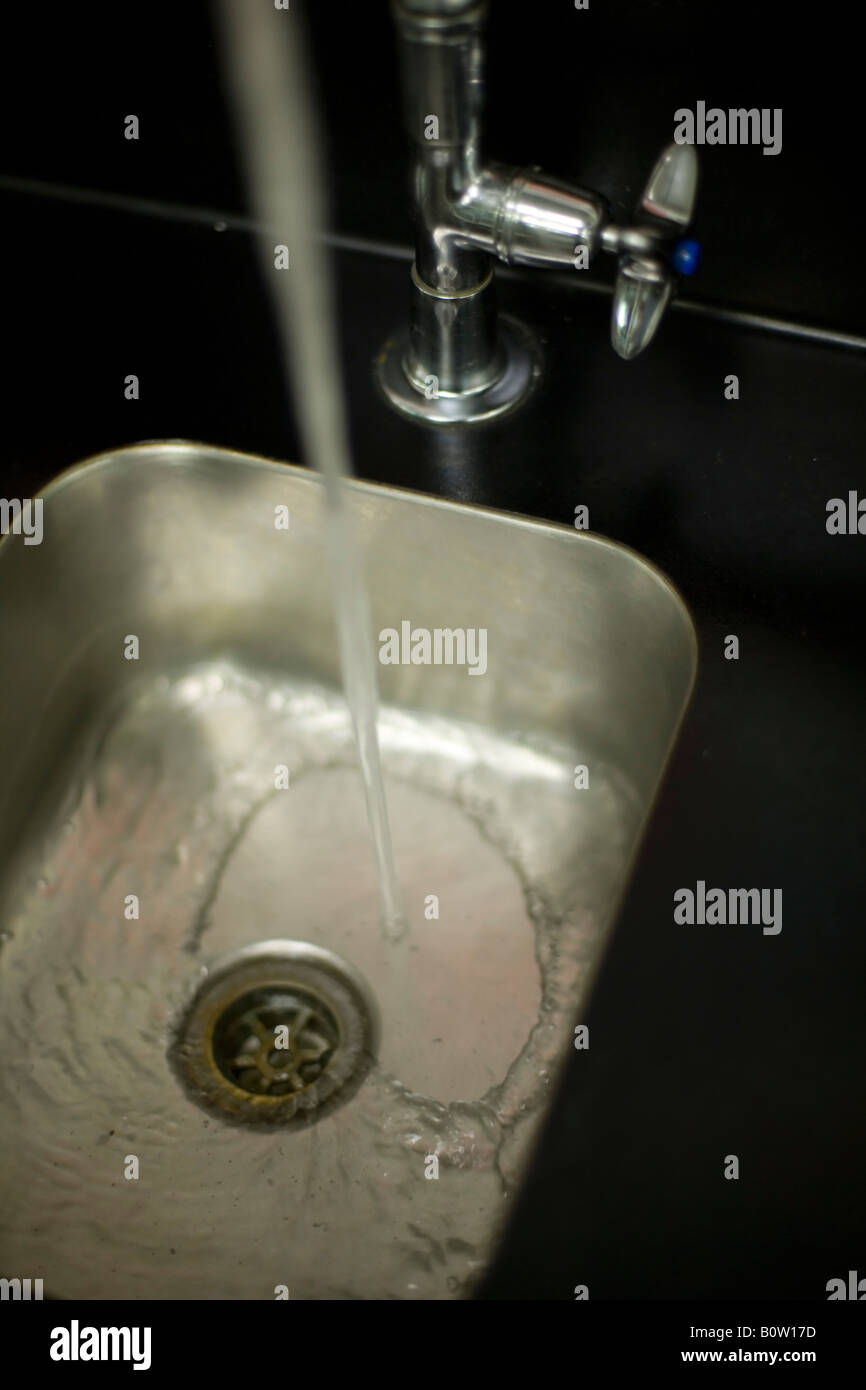 Stainless steel laboratory sink with running water Stock Photo