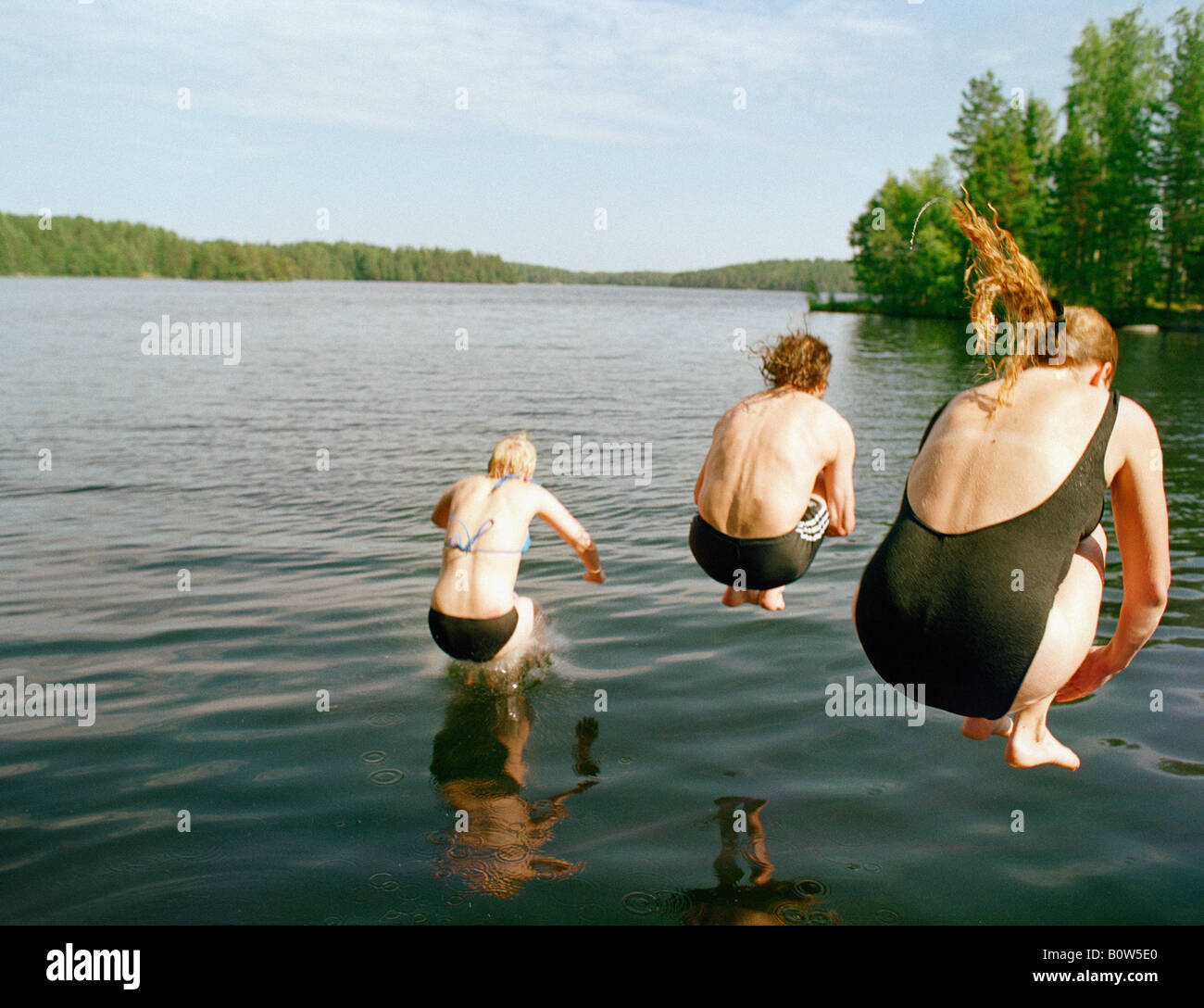 Rear view of two women and one man jumping into a lake Finland - Stock Image