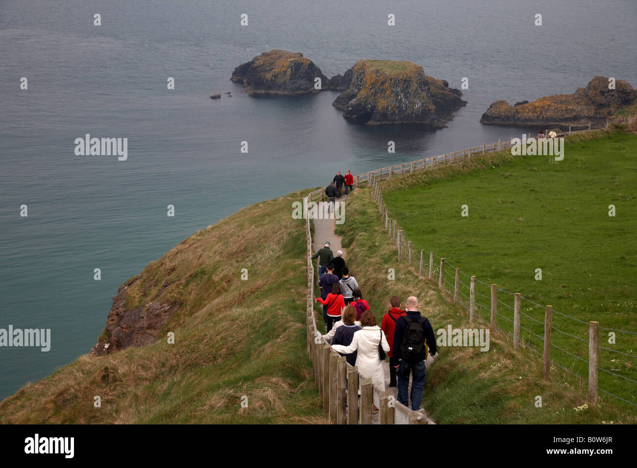 tourists walking down the long pathway to the carrick a rede rope bridge on the county antrim coast northern ireland Stock Photo