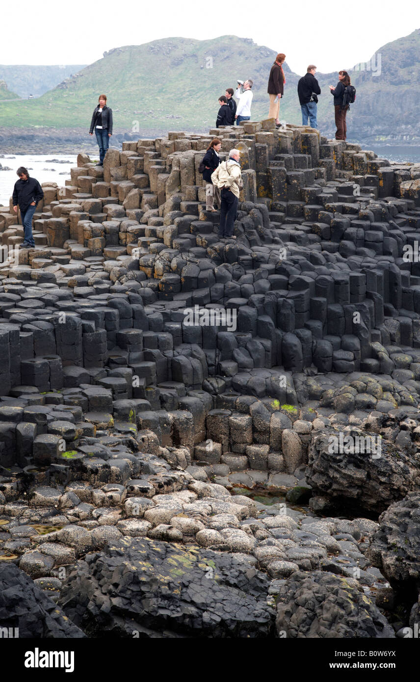 tourists wander round the red basalt hexagonal rock formations at the giants causeway county antrim northern ireland - Stock Image