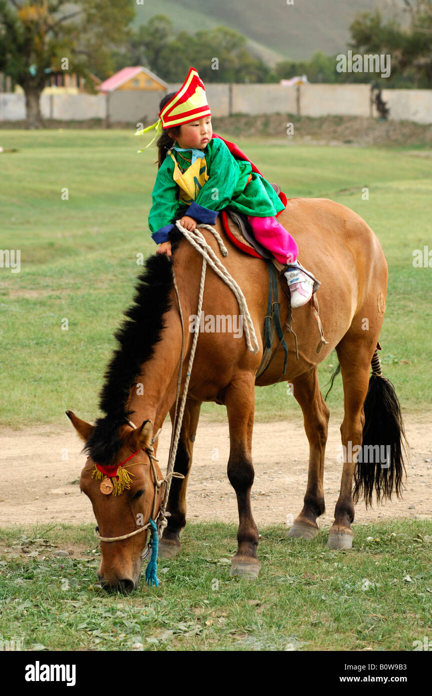 Four-year-old girl riding a horse, participant in the horsemanship competition of the Naadam Festival, Mongolia, - Stock Image