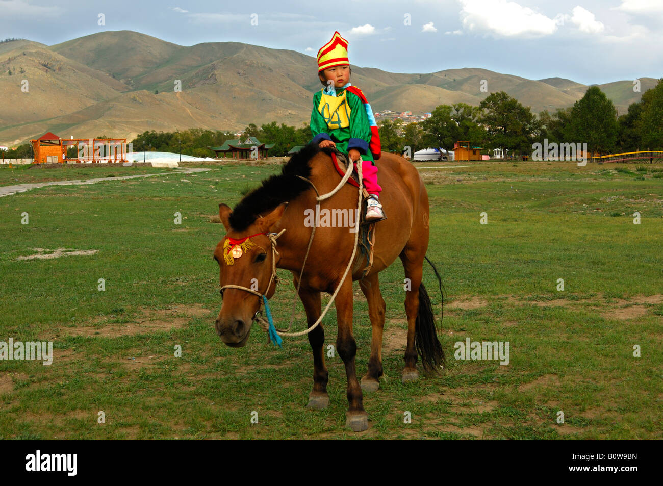 Four-year-old girl riding a horse, participant in the horsemanship competitions of the Naadam Festival, Mongolia, - Stock Image