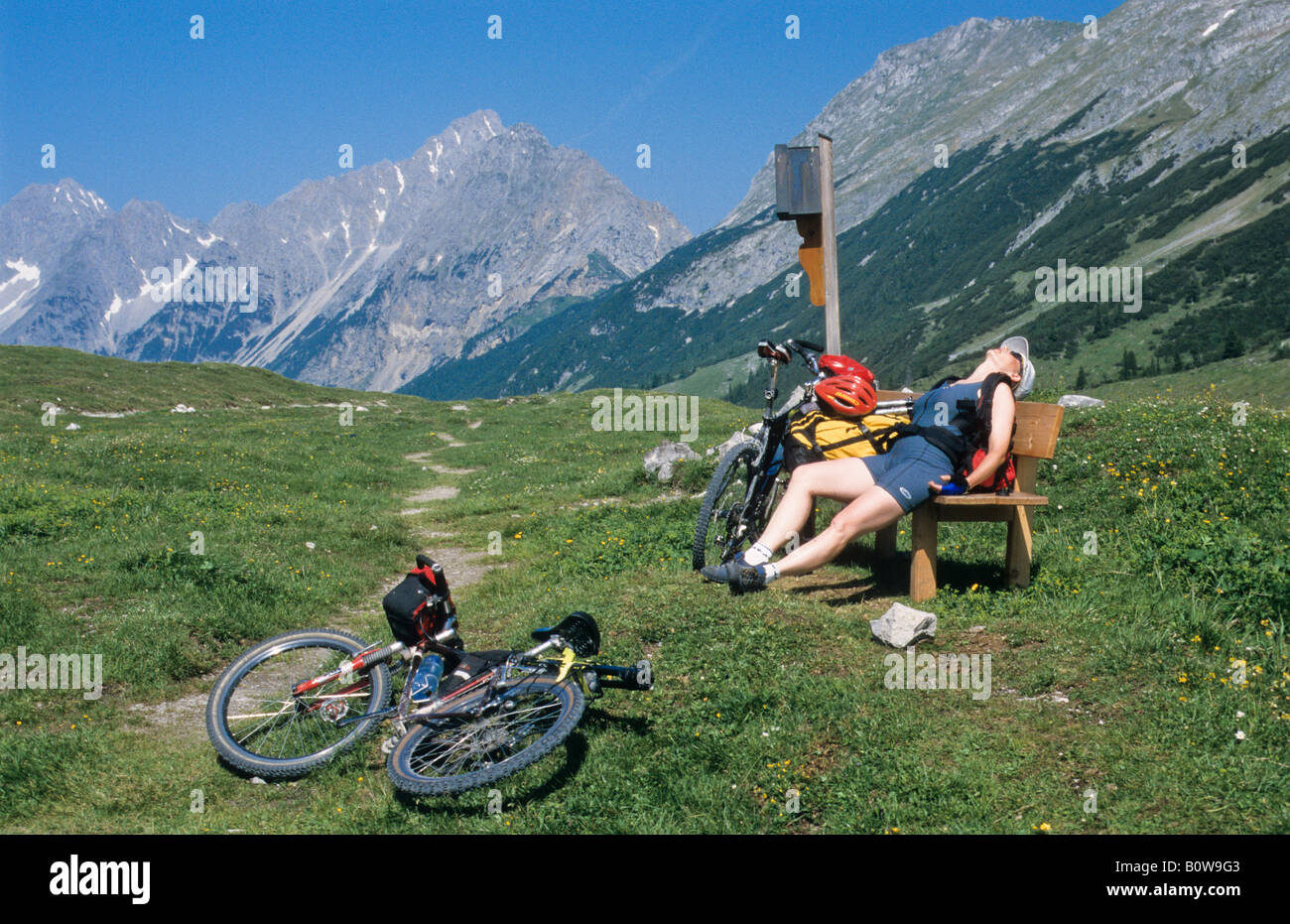 Exhausted female cyclist wearing grey cycling tricot sitting on a wooden bench, imountain bike in the grass, Karwendel - Stock Image