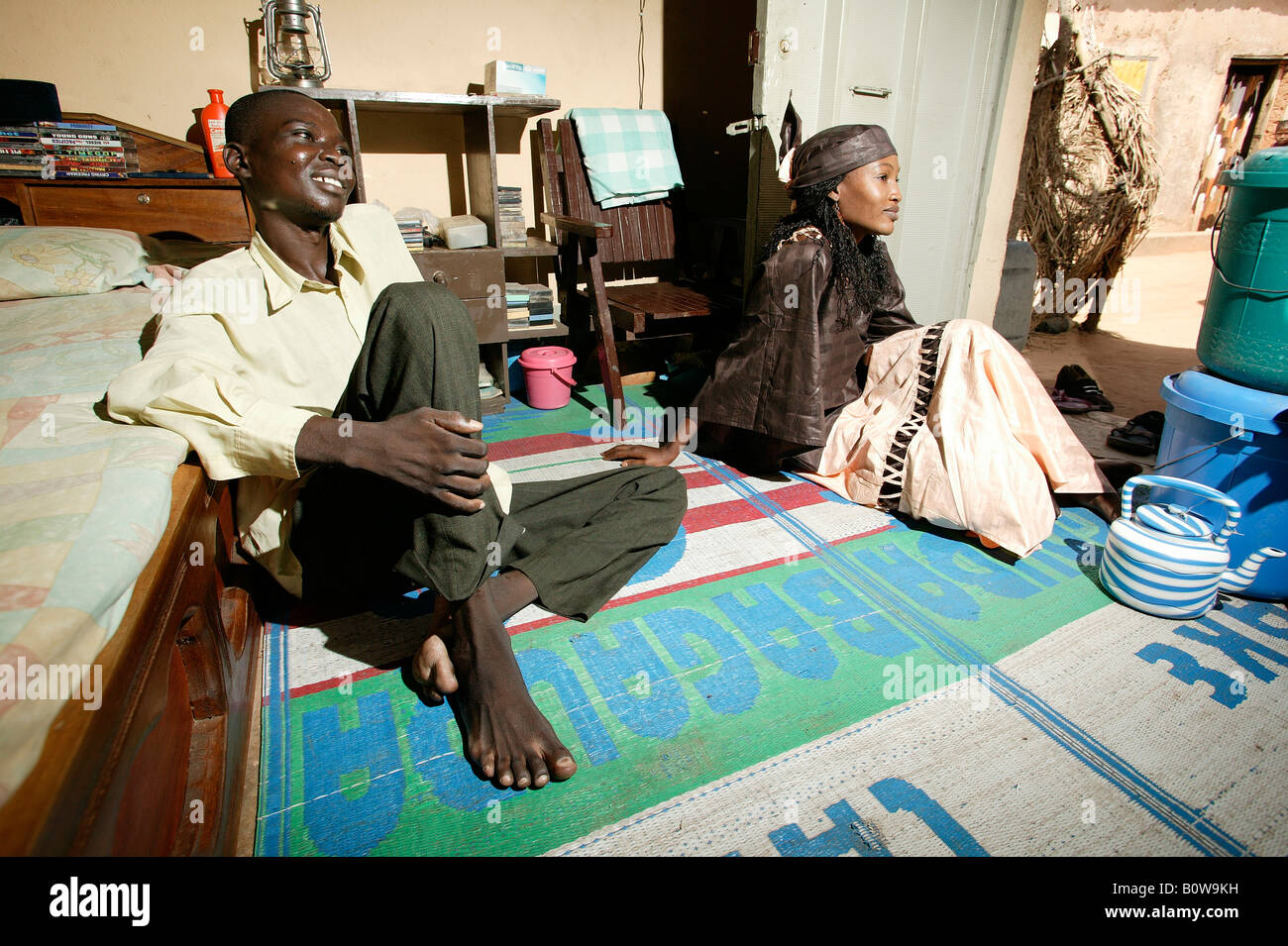 Man and woman sitting in a living room, Garoua, Cameroon, Africa - Stock Image