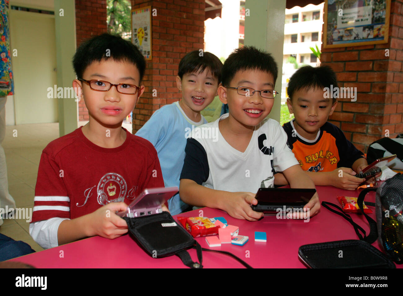 Boys playing Gameboy, Singapore, Southeast Asia - Stock Image