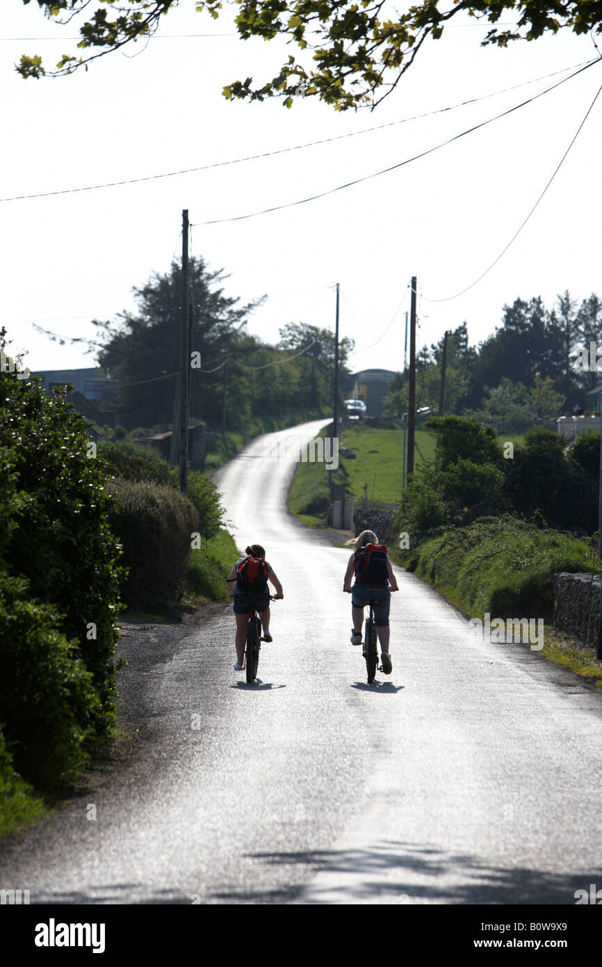 two teenage girls cycling off into the sun along a small narrow country road in county sligo republic of ireland Stock Photo