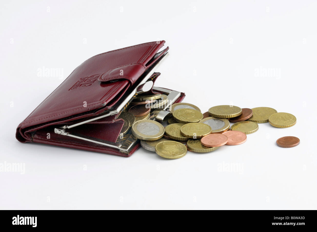 Red change purse filled with Euro coins - Stock Image