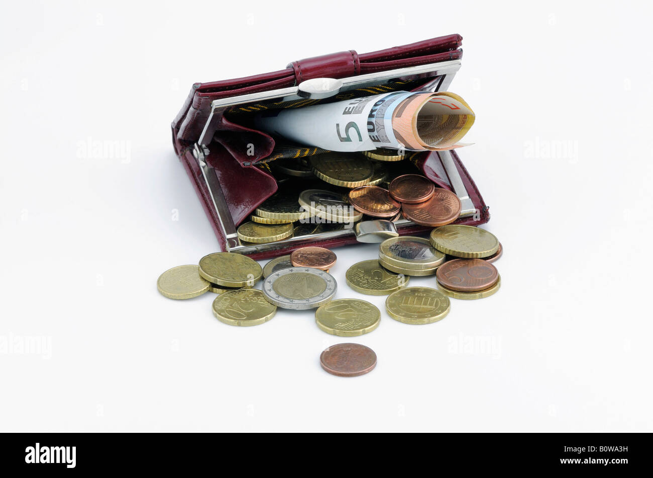 Red change purse filled with Euro coins and bills - Stock Image