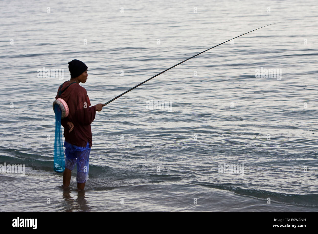 Fisherman fishing in the rain on the shore of Lombok Island