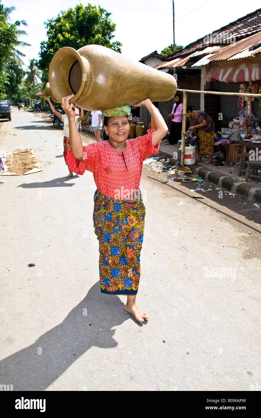 Woman carrying a traditionally crafted jar on her head, Banyumulek, Lombok Island, Lesser Sunda Islands, Indonesia - Stock Image