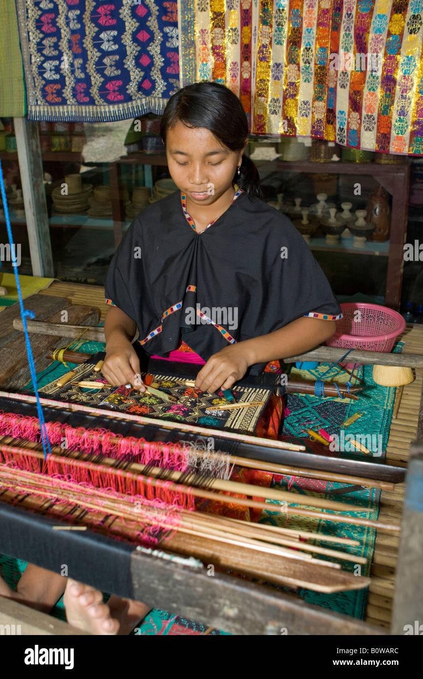 Woman weaving cloth in the traditional method on an old loom, Tete Batu, Lombok Island, Lesser Sunda Islands, Indonesia - Stock Image