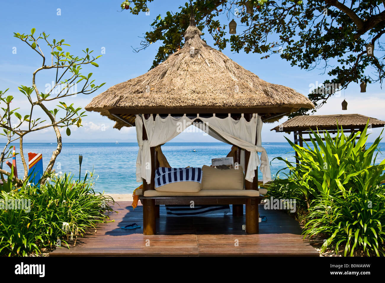 Sunlounger or thatch-roofed deck chair beside the beach of the Sheraton Hotel near Senggigi, Lombok Island, Lesser - Stock Image