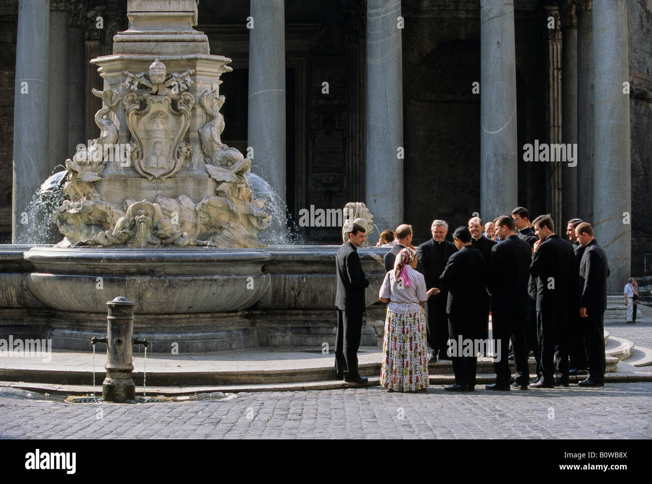 Woman begging from clerics, priests, Pantheon, Fontana di Pantheon, Piazza della Rotonda, Rome, Latium, Italy - Stock Image