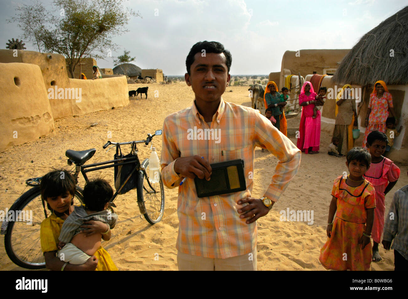 Young Indian man holding a radio standing in front of a bicycle among other people in a village in the Thar Desert - Stock Image