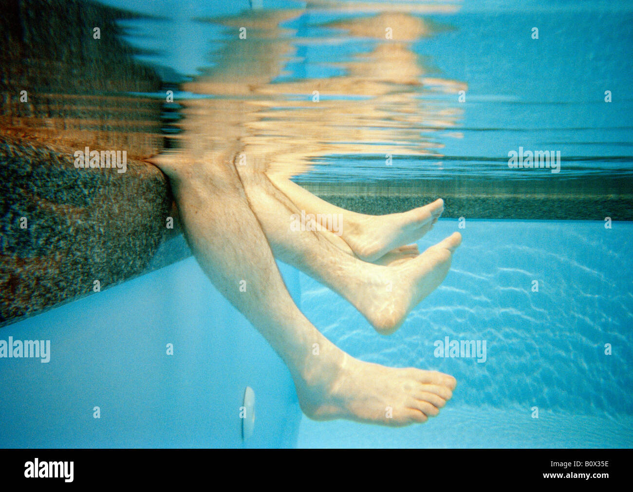 Four human legs underwater in a swimming pool - Stock Image