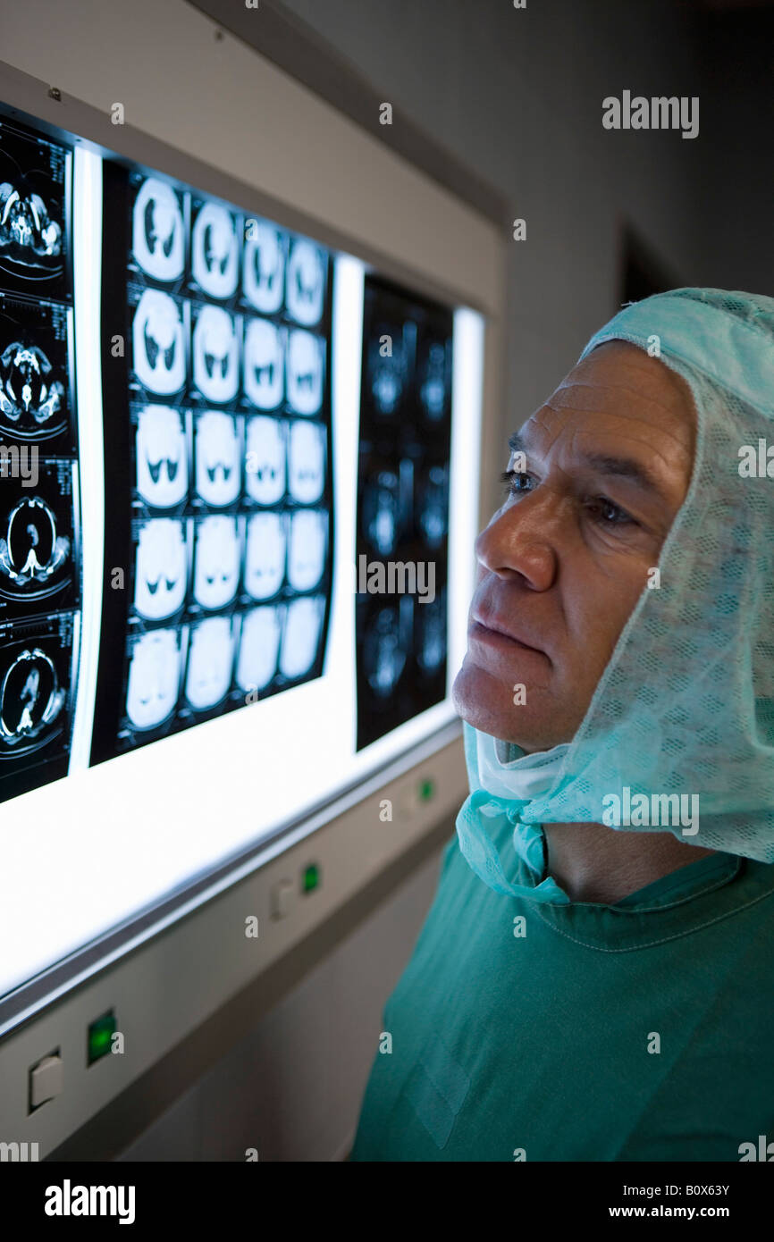 A surgeon looking at a lightbox with x-rays - Stock Image