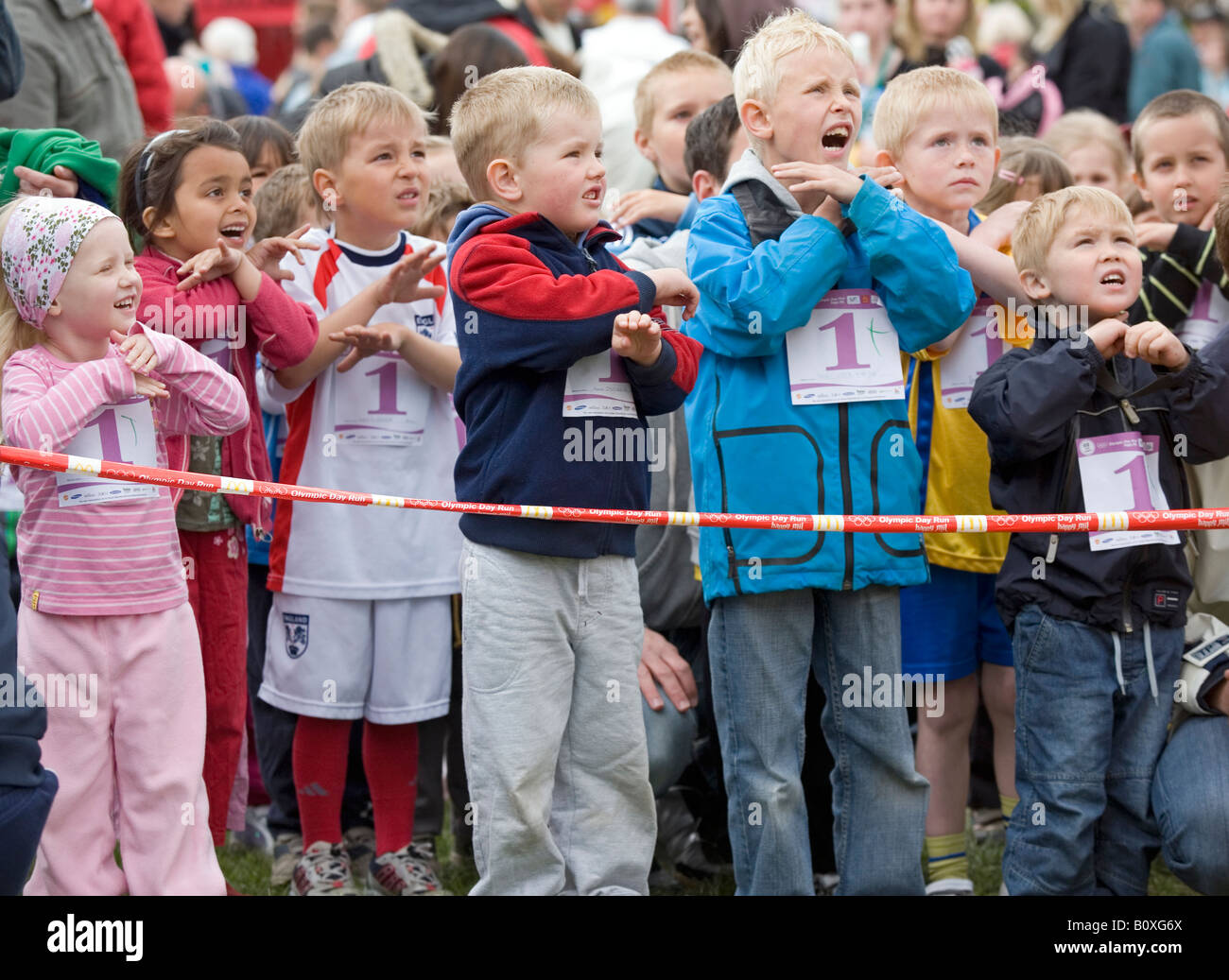 Children up to 6 years of age on start line with start numbers on warming up to run a race Stock Photo