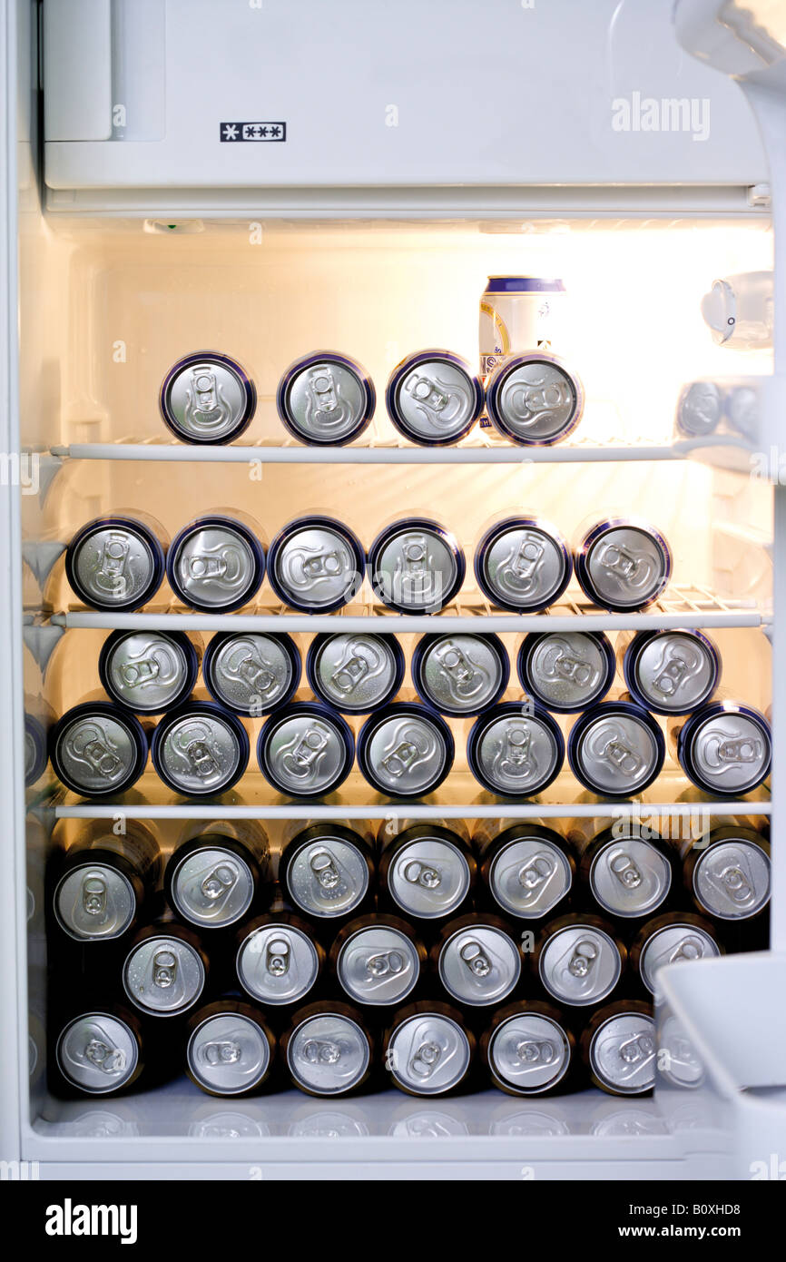 Fridge filled with cans of beer - Stock Image