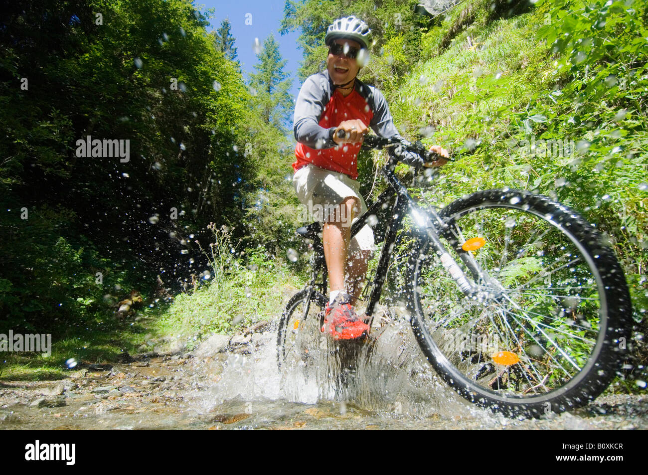 Mountainbiker crossing water - Stock Image