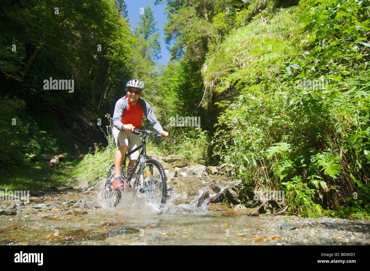 Mountainbiker crossing brook - Stock Image