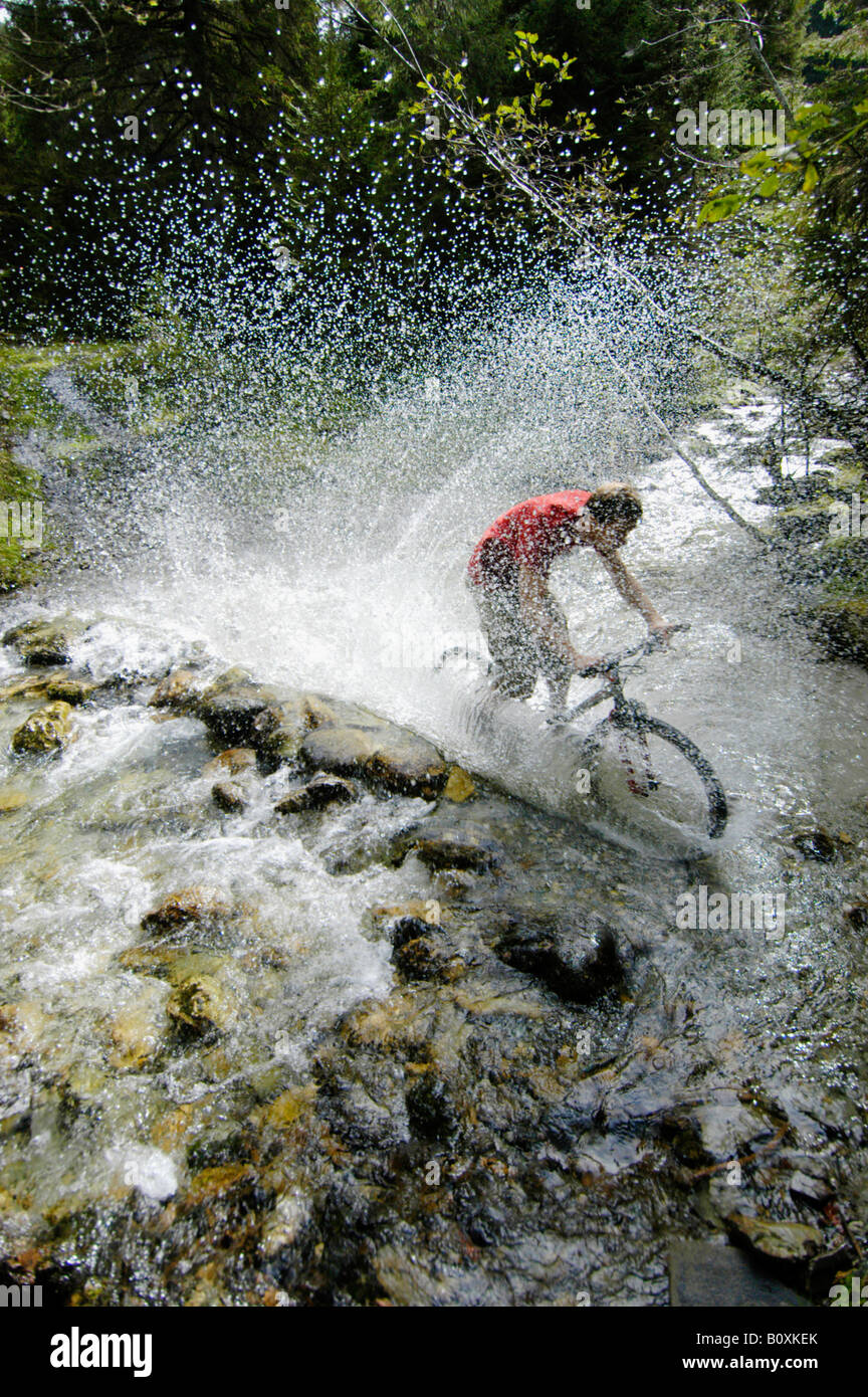 Mountainbiker crossing a creek - Stock Image