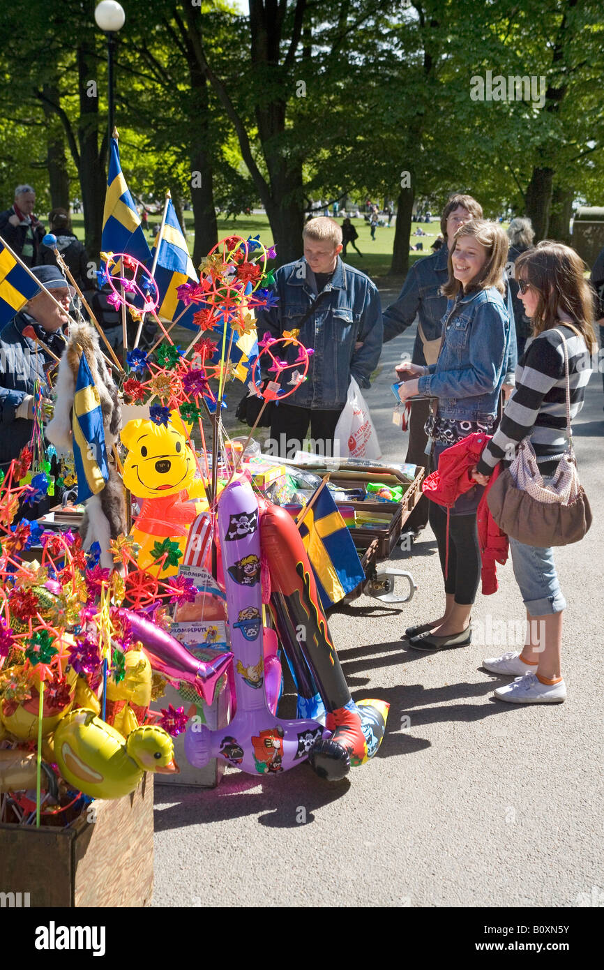 Teenage girls attracted to street vendor s stall with flags and funnies in a Park in Gothenburg Sweden - Stock Image