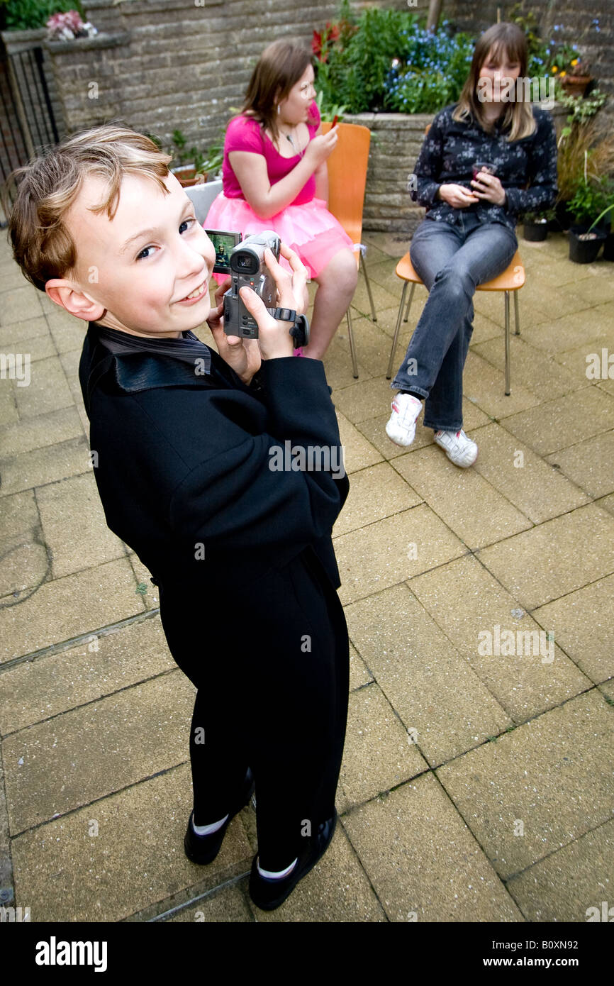 young boy in suit using video camera (camcorder) Stock Photo