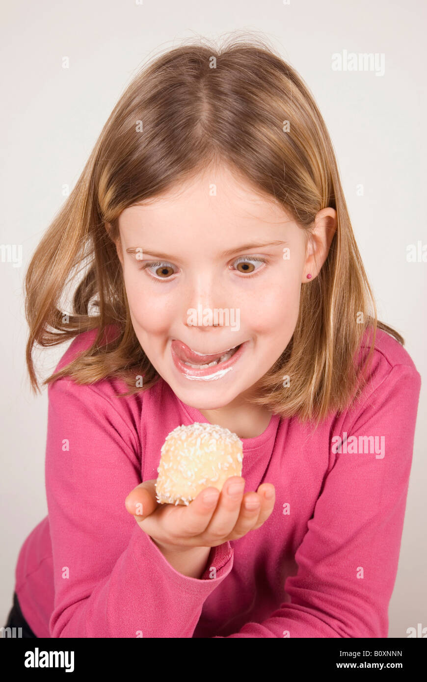 Girl (6-7) looking at chocolate marshmallows, fooling about - Stock Image
