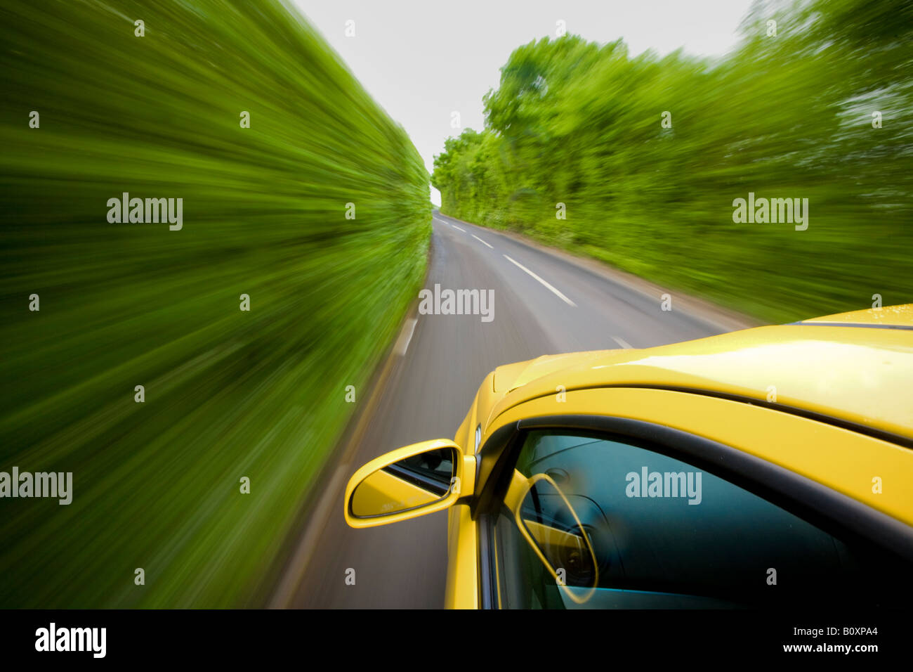 Yellow car traveling down country lane at speed with lots of blur. - Stock Image