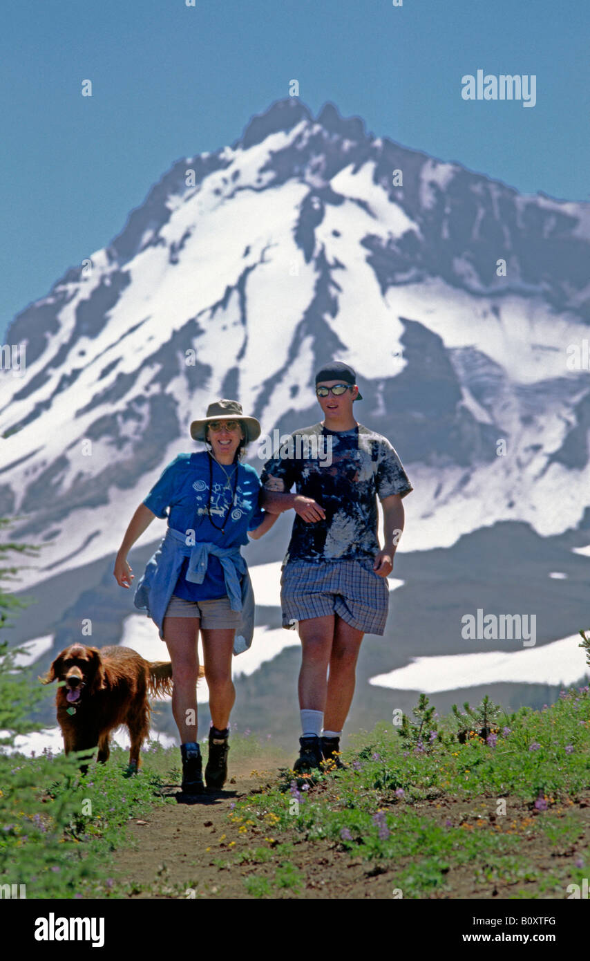 Two hikers and their Irish setter hike in the Oregon Cascades with the North Sister as a back drop, USA, Oregon, Stock Photo
